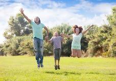 Familia con el adolescente que salta en parque Imágenes de archivo libres de regalías