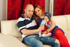 Familia con el bebé en el sofá Fotos de archivo