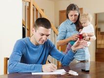 Familia con el bebé que tiene pelea de la pelea sobre el dinero imagen de archivo