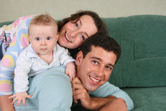 Familia con el bebé en el sofá 2 Imágenes de archivo libres de regalías
