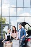 Familia con el carro de la compra al lado del coche Imagen de archivo