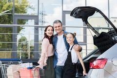 Familia con el carro de la compra al lado del coche Imágenes de archivo libres de regalías