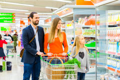 Familia con el carro de la compra en supermercado Fotos de archivo libres de regalías