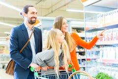 Familia con el carro de la compra en supermercado Foto de archivo