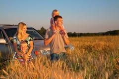 Familia con el coche campo a través en campo de trigo Foto de archivo libre de regalías