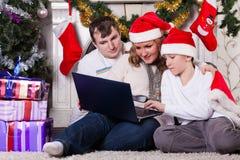 Familia con el cuaderno cerca del árbol de navidad. Fotos de archivo