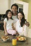 Familia con el desayuno en la tabla de cocina Imagen de archivo libre de regalías