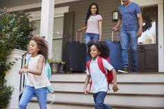 Familia con el equipaje que sale de la casa para las vacaciones imagen de archivo