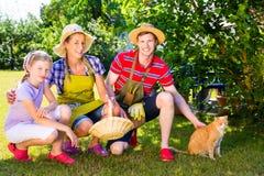 Familia con el gato que cultiva un huerto en jardín Fotos de archivo