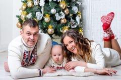 Familia con el hijo cerca del árbol de abeto del ` s del Año Nuevo que presenta y que miente Fotos de archivo