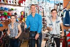 Familia con el hijo del adolescente en tienda de la bici Imagen de archivo