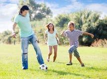 Familia con el hijo del adolescente que juega con el balón de fútbol Foto de archivo libre de regalías