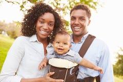 Familia con el hijo del bebé en el portador que camina a través de parque Imágenes de archivo libres de regalías