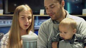 Familia con el hijo del bebé que elige aparatos electrodomésticos en la tienda metrajes