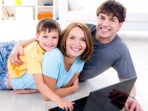 Familia con el hijo en el suelo con la computadora portátil Foto de archivo