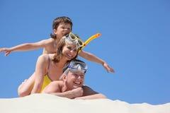 Familia con el hijo en la arena con la máscara que bucea Imagen de archivo libre de regalías