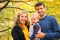Familia con el muchacho en parque del otoño Foto de archivo libre de regalías