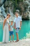 Familia con el muchacho por el río Foto de archivo