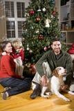 Familia con el muchacho y el perro por el árbol de navidad Fotografía de archivo libre de regalías