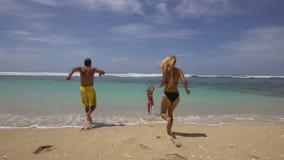 Familia con el niño en la playa almacen de metraje de vídeo