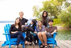 Familia con el niño especial de las necesidades que se sienta al aire libre junto en suma imagen de archivo libre de regalías