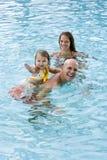 Familia con el niño joven que juega en piscina Foto de archivo