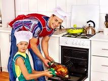 Familia con el niño que cocina el pollo en la cocina Imagen de archivo libre de regalías