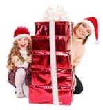 Familia con el niño que da el rectángulo de regalo rojo de la pila. Fotos de archivo