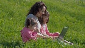 Familia con el ordenador portátil en el parque Mamá con las hijas en hierba verde con el ordenador portátil almacen de metraje de vídeo