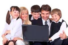 Familia con el ordenador portátil Foto de archivo