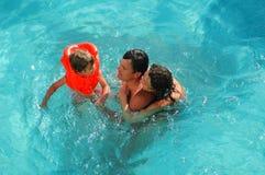 Familia con el pequeño niño en agua imagen de archivo