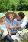 Familia con el pequeño perro blanco foto de archivo