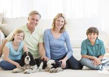 Familia con el perro casero que se sienta en piso en sala de estar
