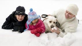 Familia con el perro que juega en nieve Imágenes de archivo libres de regalías