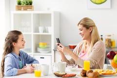 Familia con el smartphone que desayuna en casa Foto de archivo libre de regalías