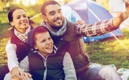 Familia con el smartphone que toma el selfie en el sitio para acampar Imágenes de archivo libres de regalías
