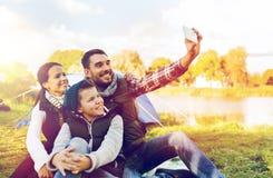 Familia con el smartphone que toma el selfie en el sitio para acampar Imagen de archivo libre de regalías