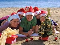 Familia con el sombrero de Papá Noel en la playa Fotos de archivo