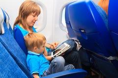 Familia con la almohadilla táctil en el avión Imagen de archivo libre de regalías