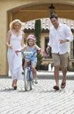 Familia con la bici del montar a caballo de la muchacha y padres felices Fotos de archivo