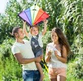 Familia con la cometa del juguete en el parque Imagen de archivo