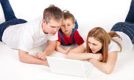 Familia con la computadora portátil Fotografía de archivo libre de regalías