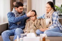 Familia con la hija enferma que tiene fiebre en casa fotos de archivo libres de regalías