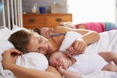 Familia con la mentira del bebé dormida en cama junto fotos de archivo