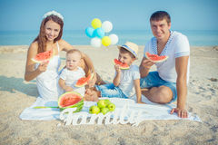 Familia con la sandía en la playa Fotos de archivo