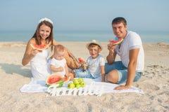 Familia con la sandía en la playa Imagen de archivo