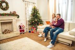 Familia con la tableta digital en la tarde de la Navidad Fotografía de archivo libre de regalías