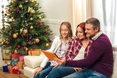 Familia con la tableta digital en la tarde de la Navidad Imagenes de archivo