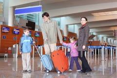 Familia con las maletas en pasillo del aeropuerto Fotos de archivo libres de regalías