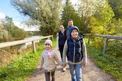 Familia con las mochilas que caminan o que caminan en bosque imagenes de archivo